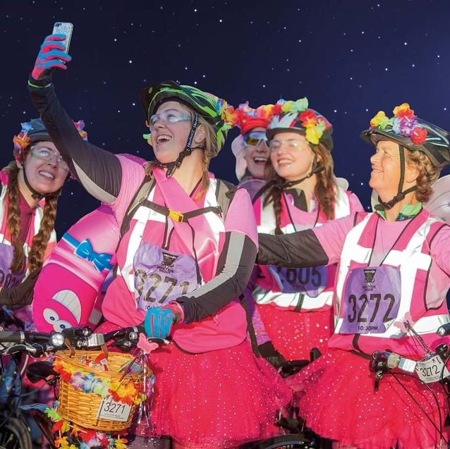Group of women in pink high visibility vests taking a selfie with their bikes at night in London