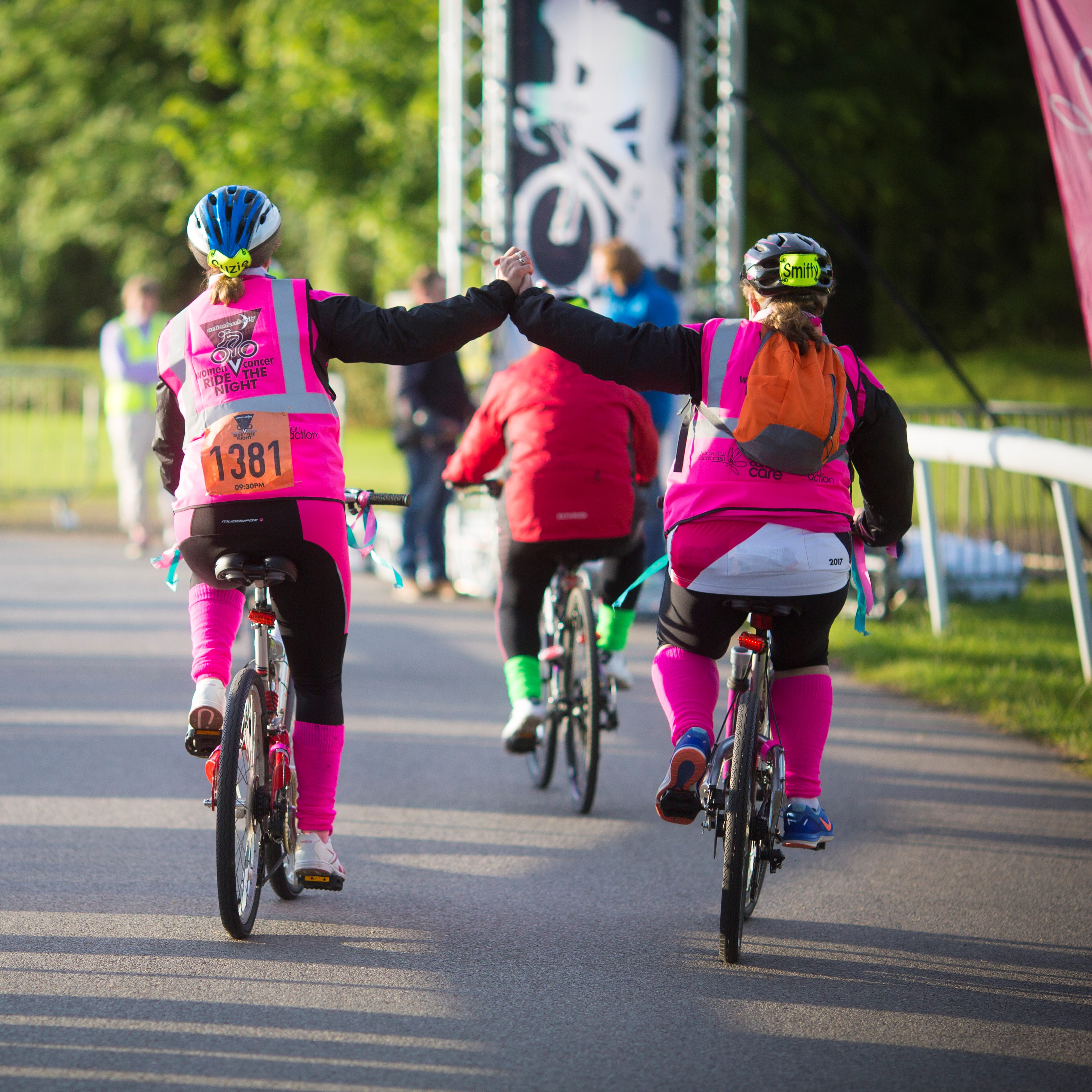 Women V Cancer Ride the Night participants high fiving in celebration of conquering a 100 km cycling challenge in London to raise money for Ovarian Cancer Action, Breast Cancer Care and Jo's Cervical Cancer Trust.