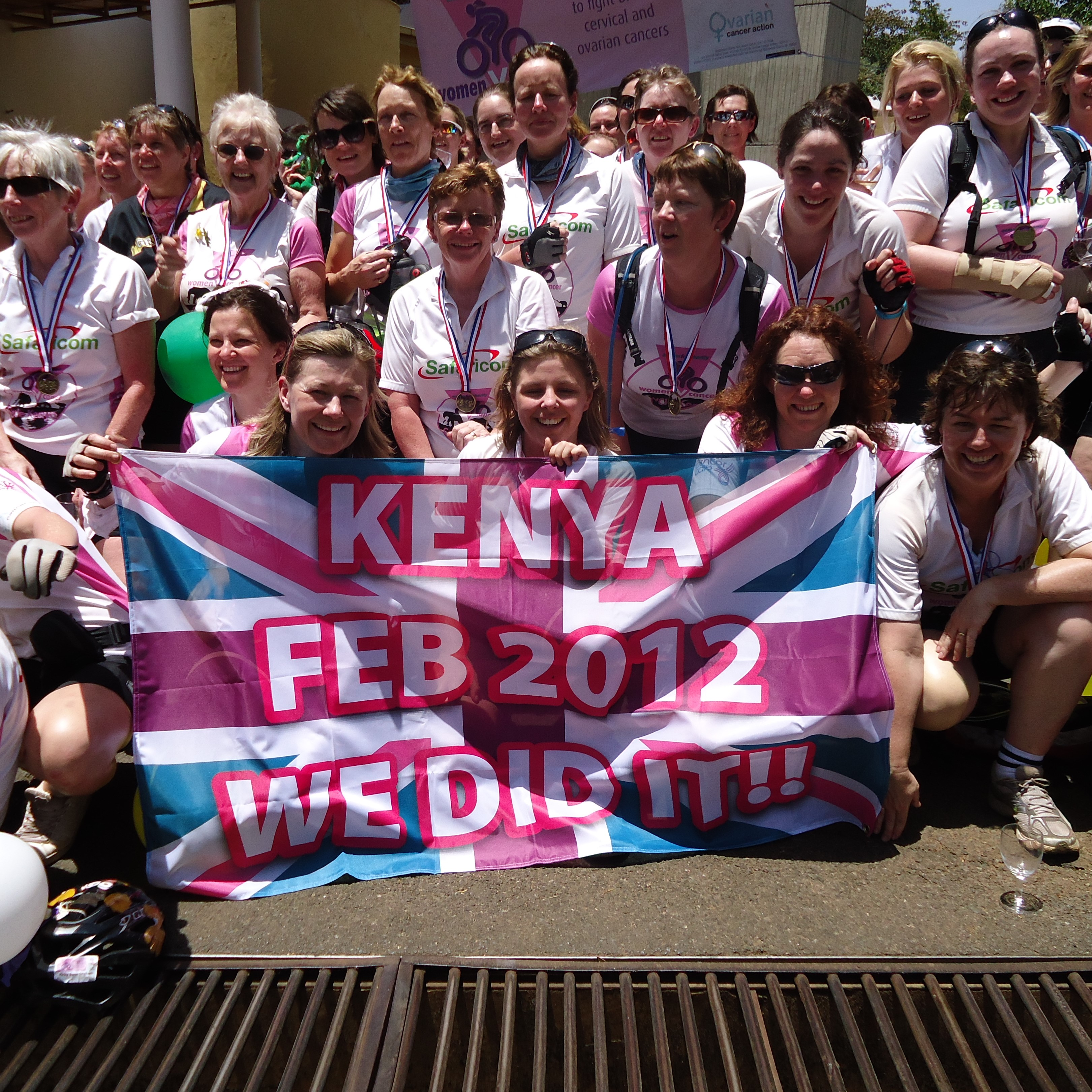 "Group of women celebrate with a pink union jack flag saying ""We did it! Kenya Feb 2012"" in Kenya"