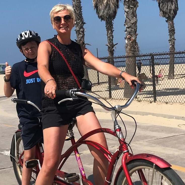 Jo Whitely with her son cycling on a beach, preparing for Women V Cancer Ride the Night Edinburgh 2019