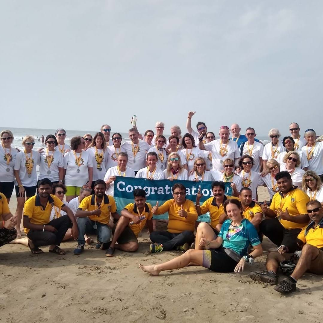 Group of men and women celebrating on a beach in Goa after completing a Dream Challenge